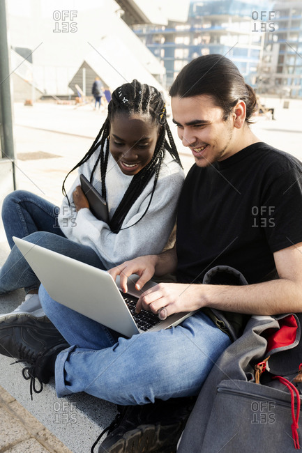 Happy young couple using laptop at tram stop