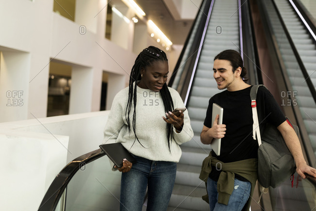 Two students with cell phone on an escalator