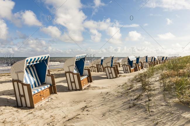 Germany- Mecklenburg-Western Pomerania- Rows of strandkorb chairs on sandy coastal beach in summer