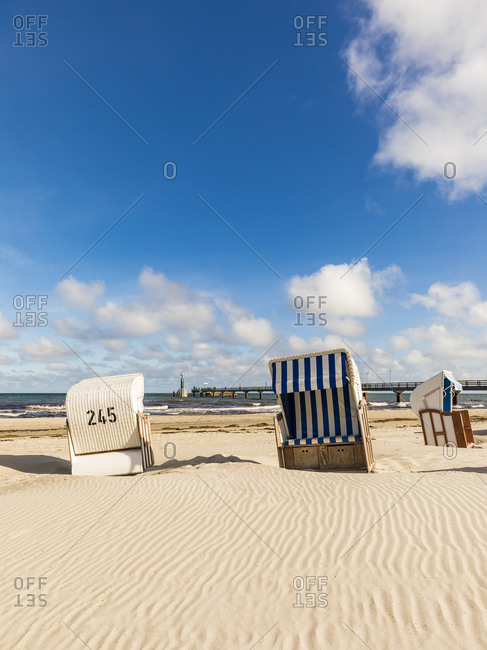 Germany- Mecklenburg-Western Pomerania- Strandkorb chairs on sandy coastal beach in summer