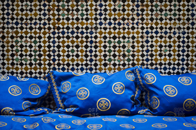Comfortable seating and a tiled wall inside a house in Fes, Morocco