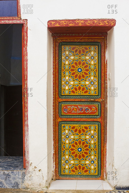 A narrow, colourfully painted door inside a house in Fes, Morocco