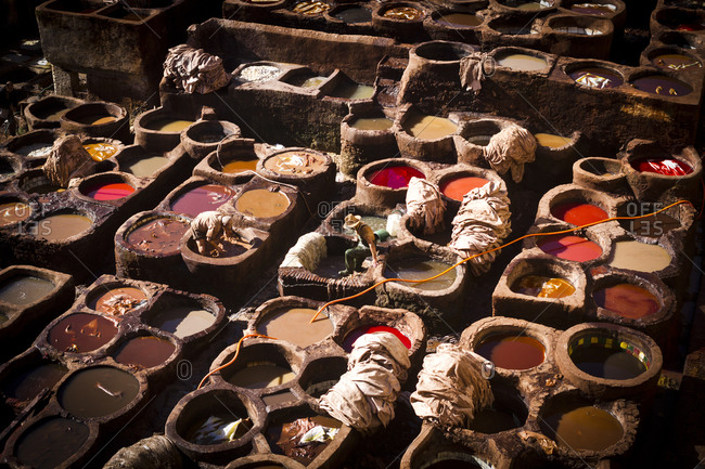 Workers tanning leather in pots of dye in the Tanners Quarter of Fes, Morocco