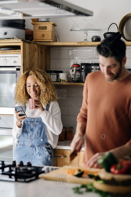 Stock photo of a middle aged woman and man standing in a kitchen. She's using her smartphone and him is cutting vegetables. They are smiling.