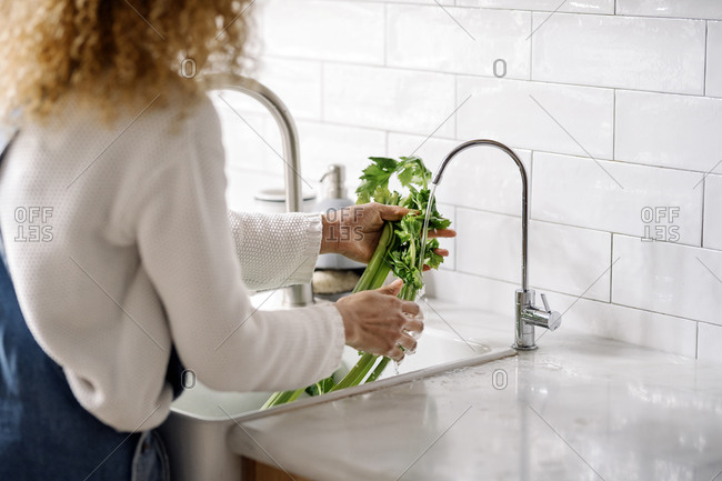 Stock photo of a middle aged woman cleaning vegetables at the tap in the kitchen. She is unrecognizable.