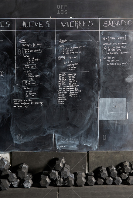 Stock photo of a workout plan written with chalk on a blackboard with a weights underneath it. There are nobody on the picture.