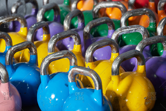 Stock photo of a bunch of colorful dumbbells from close. They are lined up. There are blue, yellow, purple, green, orange and red ones.