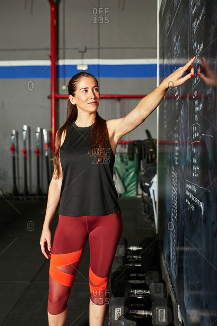 Stock photo of a caucasian woman pointing at training plans written on a chalkboard. She is wearing a black tank top and red pants.
