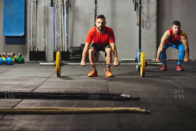 Stock photo of two adult men in a gym squatting down and lifting barbells. They are wearing sportswear. They are facing the camera.