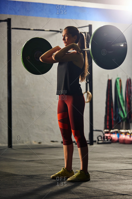 Stock photo of an adult woman in a gym standing up and lifting a barbell. She is wearing sportswear.