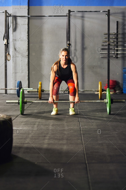 Stock photo of an adult woman in a gym squatting down and lifting a barbell. She is wearing sportswear. She is facing and looking at the camera.