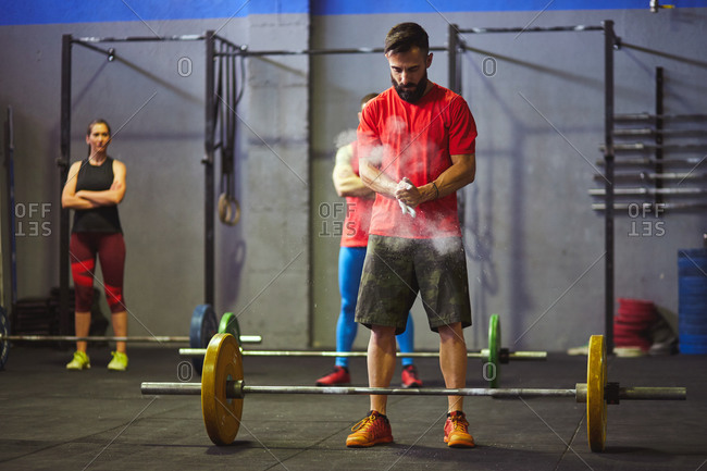 Stock photo of an adult man in a gym chalking his hands. There is a barbell in front of him and people behind him. They are wearing sportswear.