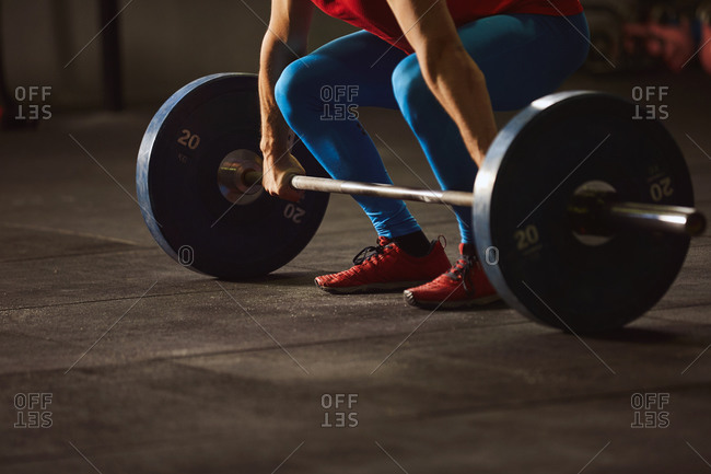 Stock photo of an adult man in a gym standing behind a barbell. He is unrecognizable. He is wearing sportswear.