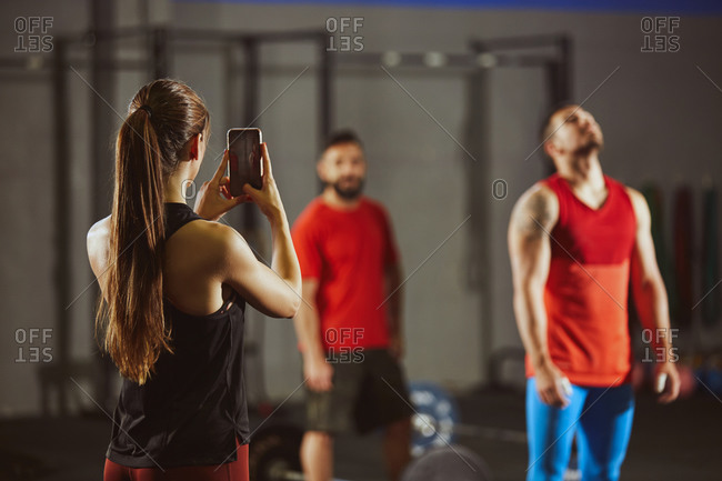 Stock photo of three adult people in a gym standing. A woman is taking a picture of two men with her smartphone. They are wearing sportswear.