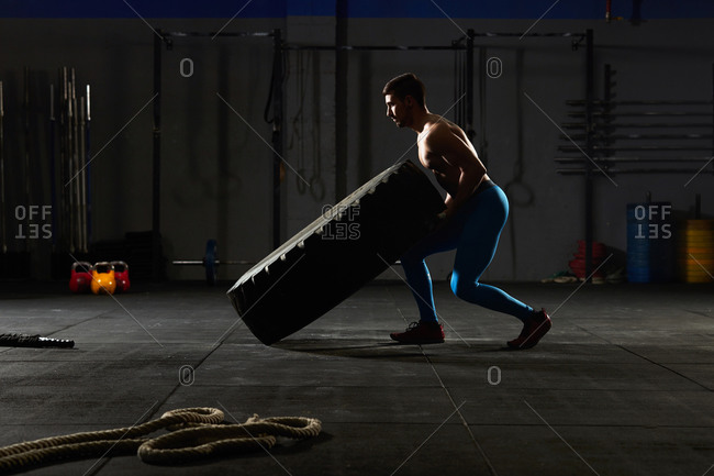 Stock photo of an adult man in a gym flipping over a tractor tire. He is wearing sportswear.