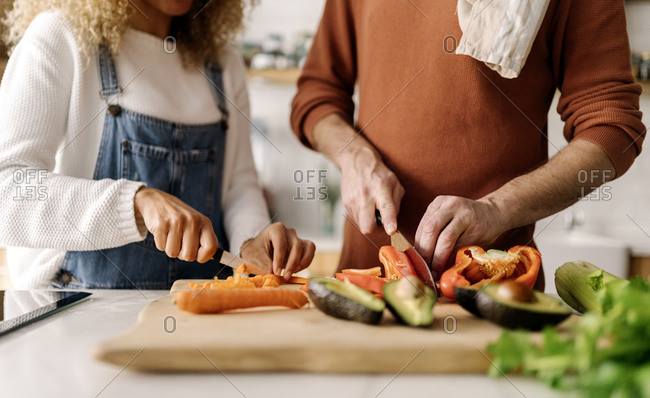 Stock photo of a middle aged woman and man preparing food in a kitchen. They are chopping up some vegetables. They are unrecognizable.