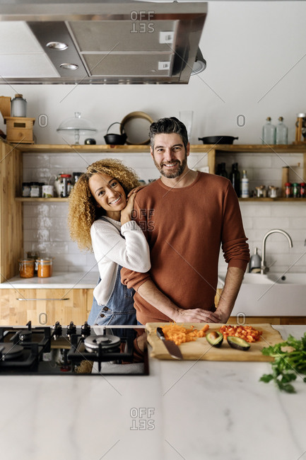 Stock photo of a middle aged woman and man standing in a kitchen and laughing. The woman is leaning on the man's shoulder.