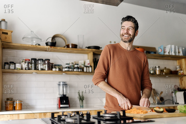 Stock photo of a middle aged man holding a knife and slicing up some vegetables in a kitchen. He is looking through a window and smiling.