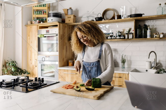 Stock photo of a middle aged woman holding a knife and slicing up some vegetables in a kitchen. She is smiling.