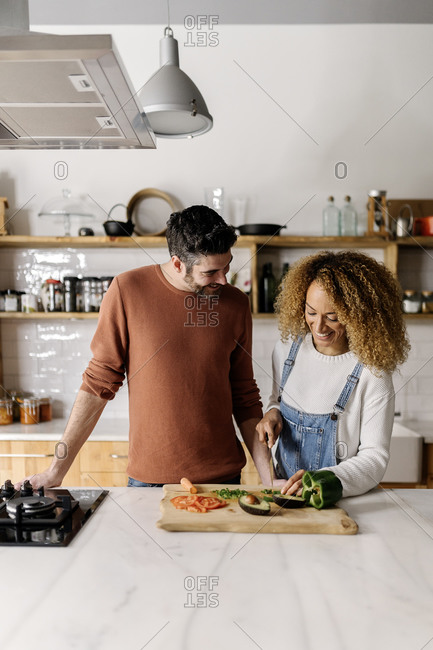 Stock photo of a middle aged woman and man preparing food in a kitchen. The woman is chopping up some vegetables.