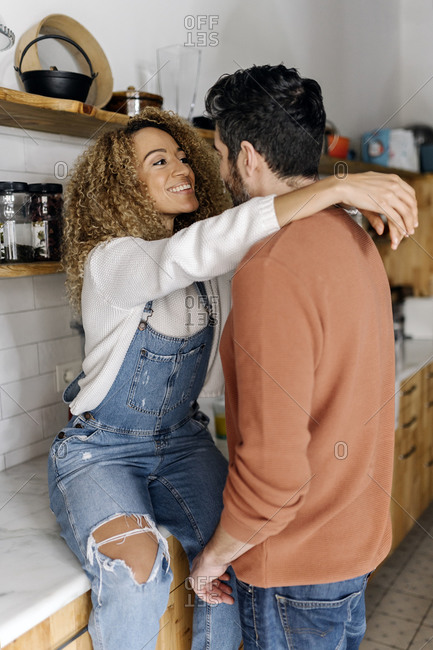 Stock photo of a middle aged woman and man standing in a kitchen and laughing. The woman is hugging the man.