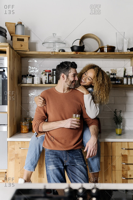 Stock photo of a middle aged woman and man standing in a kitchen and laughing. The woman is looking at the man. They are laughing.
