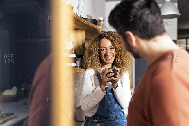 Stock photo of a middle aged woman looking at her boyfriend in a kitchen. The woman is holding a mug. The man is unrecognizable.