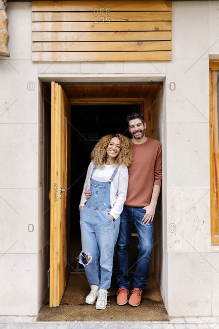 Stock photo of a middle aged woman and man standing in doorway They are looking at the camera and smiling. The man has his arms around the woman.