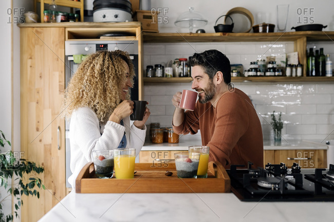 Stock photo of a middle aged woman and man having breakfast in a kitchen and laughing together. They are relaxed.