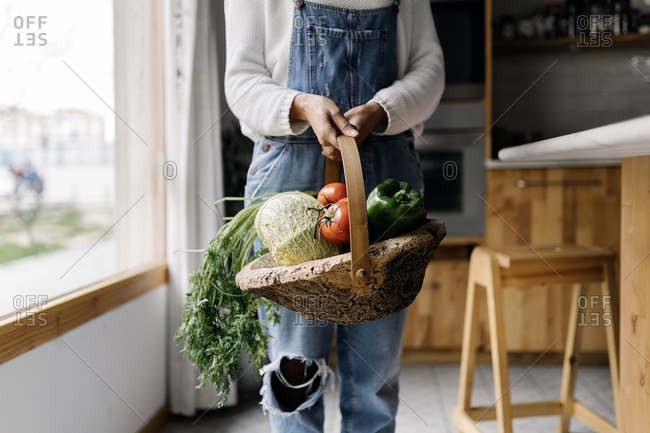 Stock photo of a middle aged woman holding a basket of vegetables in a kitchen. The woman is unrecognizable.