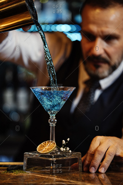 Stock photo of an expert barman making a cocktail at night club.