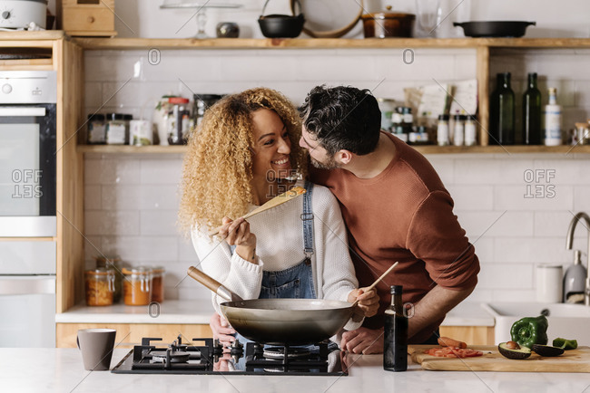 Stock photo of a middle aged woman and man cooking food in a kitchen. The woman is holding up a wooden spoon.