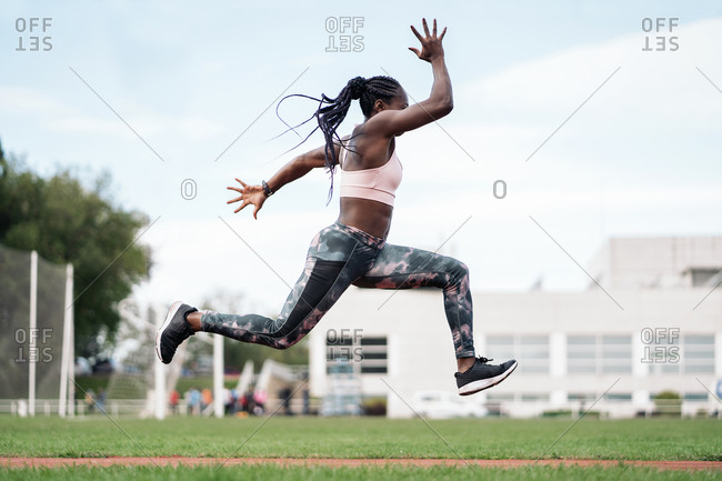 Stock photo of an African-American sprinter jumping in the sports center