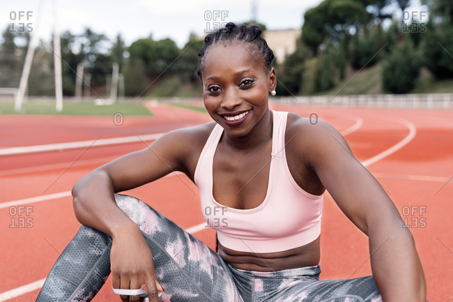 Stock photo of an African-American sprinter sitting on the athletics track in sportswear and smiling looking straight ahead