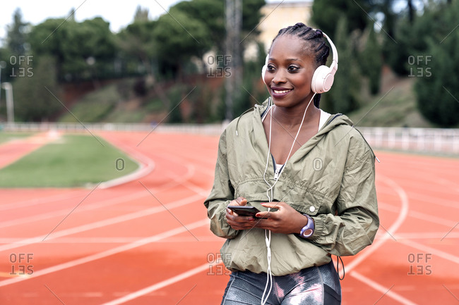 Stock photo of an African-American sprinter sitting on the athletics track with her helmets on, listening to music with her mobile phone