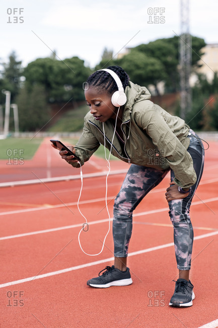 Stock photo of an African-American sprinter sitting on the athletics track with her helmets on, listening to music with her mobile phone exhausted