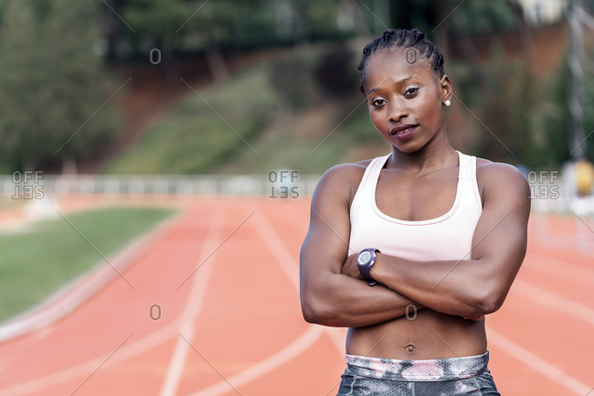 Stock photo of an African-American sprinter standing on an athletics track looking at camera straight ahead