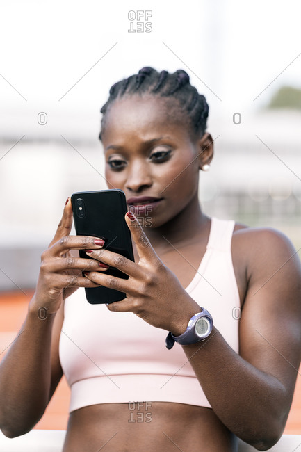 Stock photo of an African-American sprinter using her mobile phone