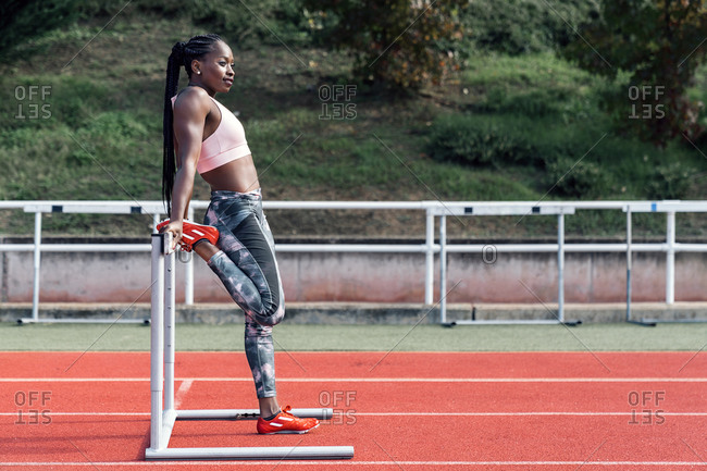 Stock photo of an African-American sprinter stretching her legs before training with a hurdle
