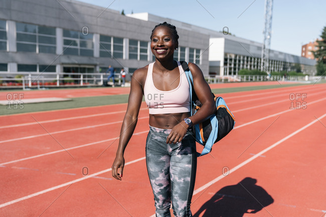 Stock photo of an African-American sprinter walking on the track with a training bag on her shoulder and a building in the background