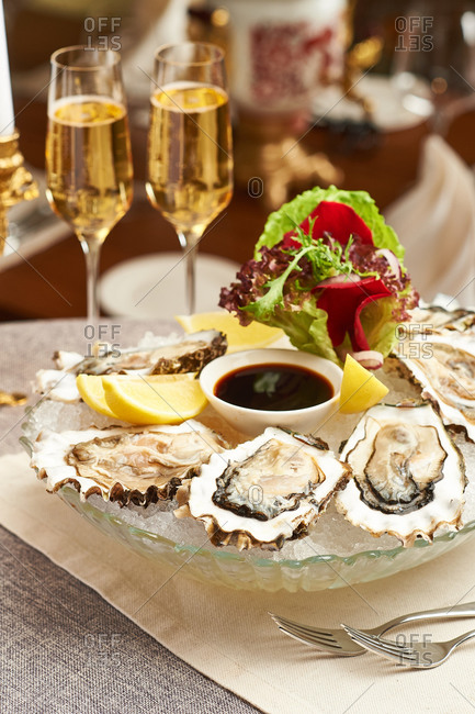 Oysters on the table with lemon, soy sauce and salad with two glasses of champagne
