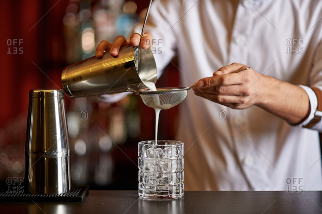 The bartender pours a cocktail through a sieve into a glass of ice on the bar counter