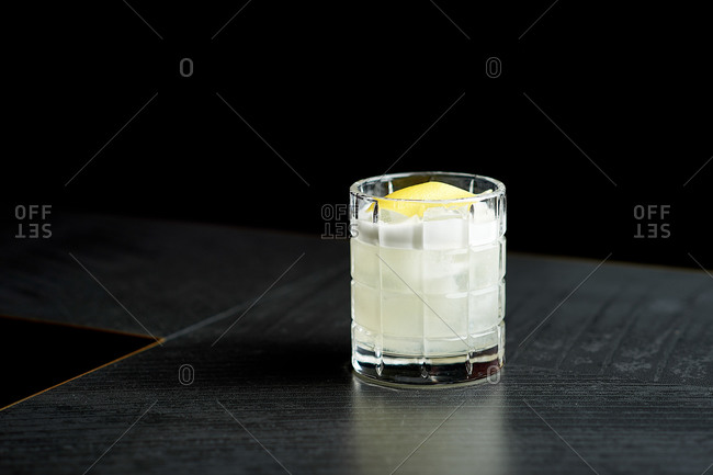 Glass with a beautiful cocktail on a black table