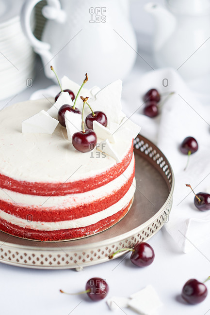 Red velvet cake with white cream and cherries on a white table