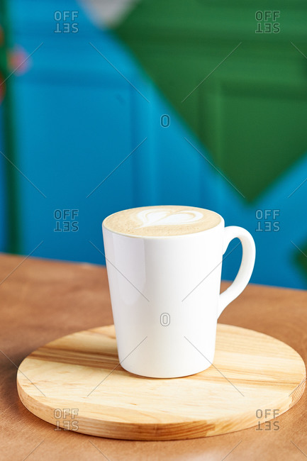 White coffee mug in a coffee shop against a colored wall