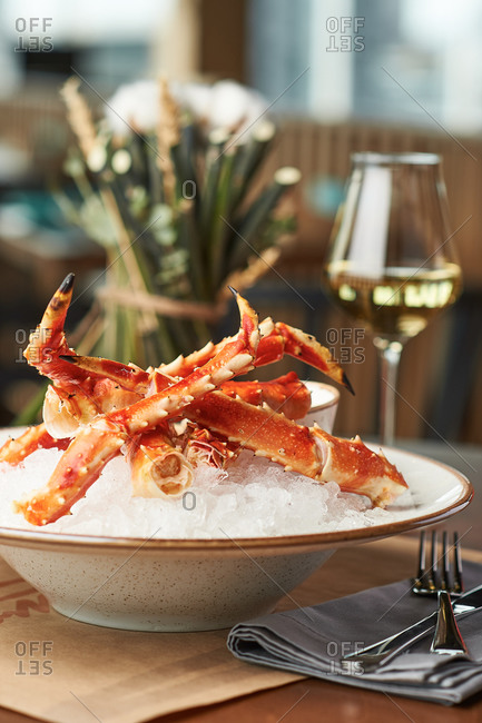 Crab claws boiled served in a restaurant on a plate with ice and a glass of white wine