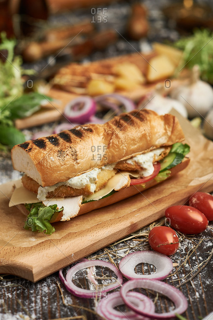 Grilled fish sandwich with cheese and cream with onions and tomatoes
