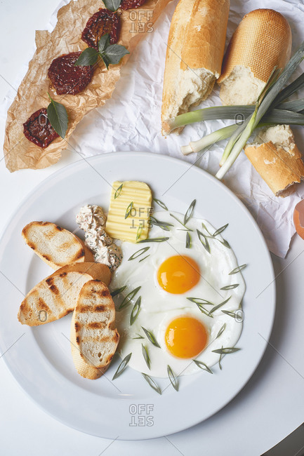 Breakfast fried eggs with toast butter sun dried tomatoes and french baguette