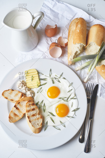 Breakfast fried eggs with toast butter and french baguette