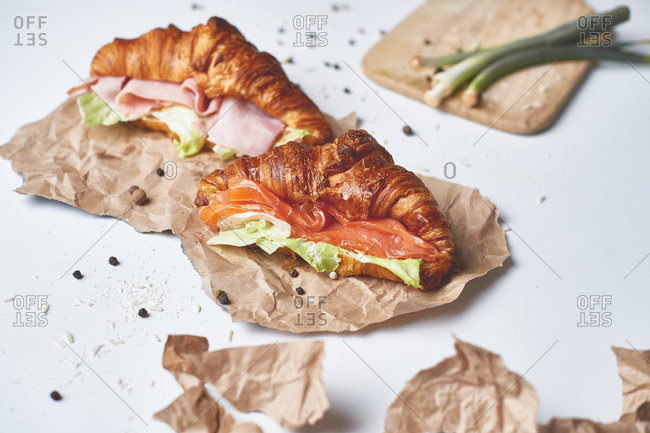 Breakfast fresh croissant with smoked salmon, salad, butter, cream cheese and ham